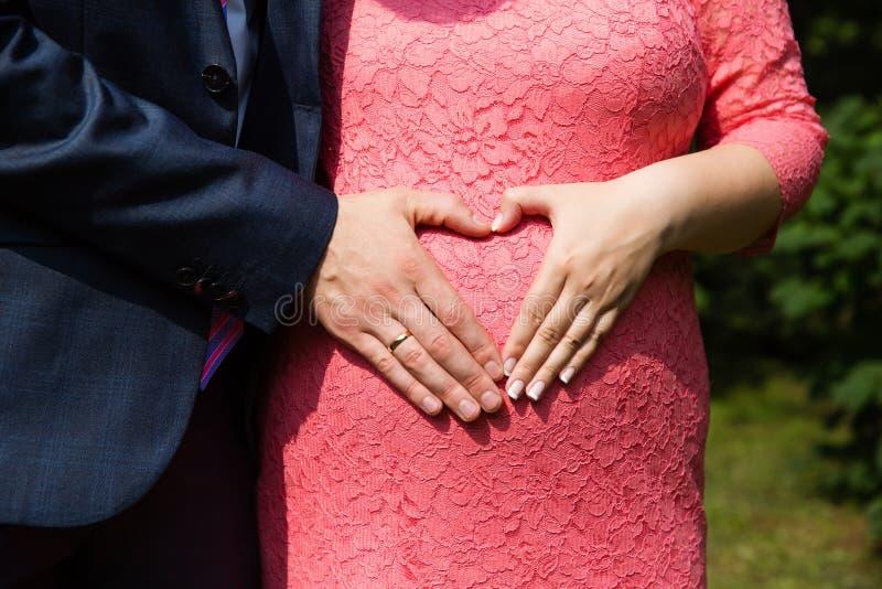 Hochzeitspaarhände mit Ringen auf dem schwangeren Bauch der Frau stockbilder