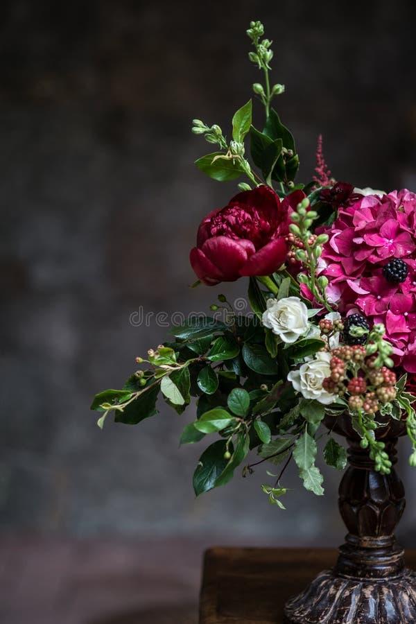 Hochzeitspfingstrosenblumenstrauß gegen Weinlesedunklen Steinhintergrund Rustikale Art stockfotos