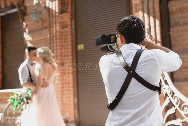 Hochzeitsphotograph macht Fotos der Braut und des Bräutigams stockbild
