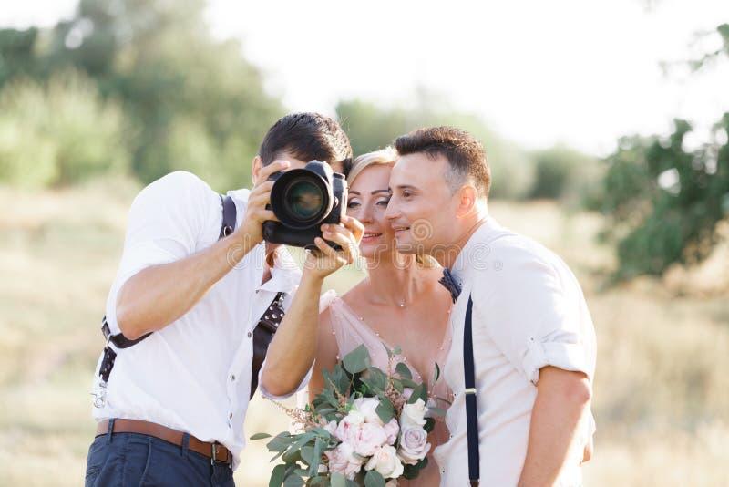 Hochzeitsphotograph macht Fotos der Braut und des Bräutigams stockfotografie