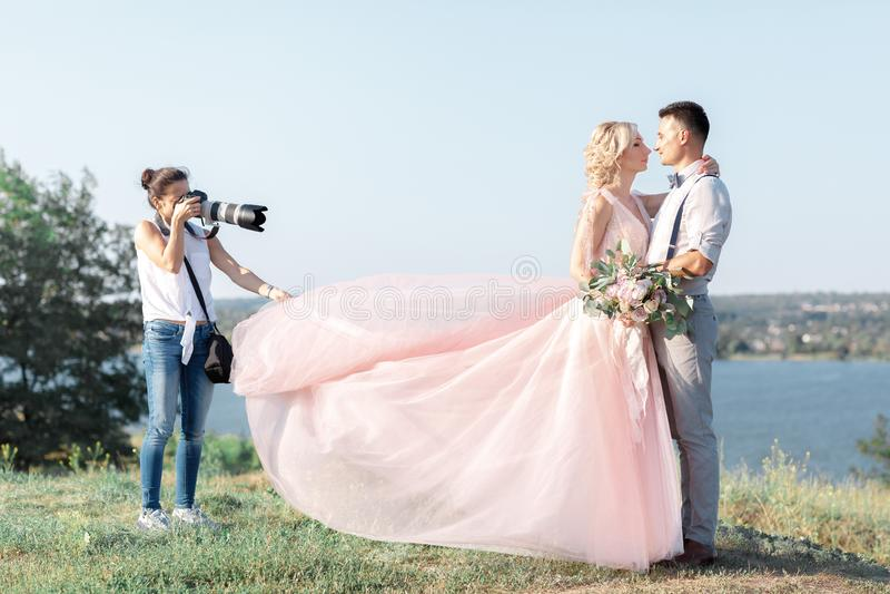 Hochzeitsphotograph macht Fotos der Braut und des Bräutigams lizenzfreies stockbild