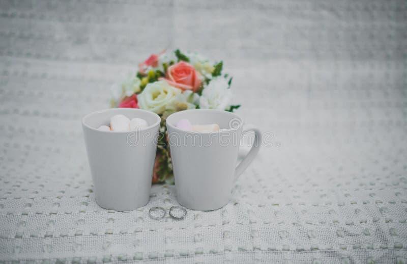 Hochzeitsphotographie Heiratsdetailwinterhochzeit zwei weiße Schalen mit und Eibische, ein Brautblumenstrauß und Ringe lizenzfreie stockfotos