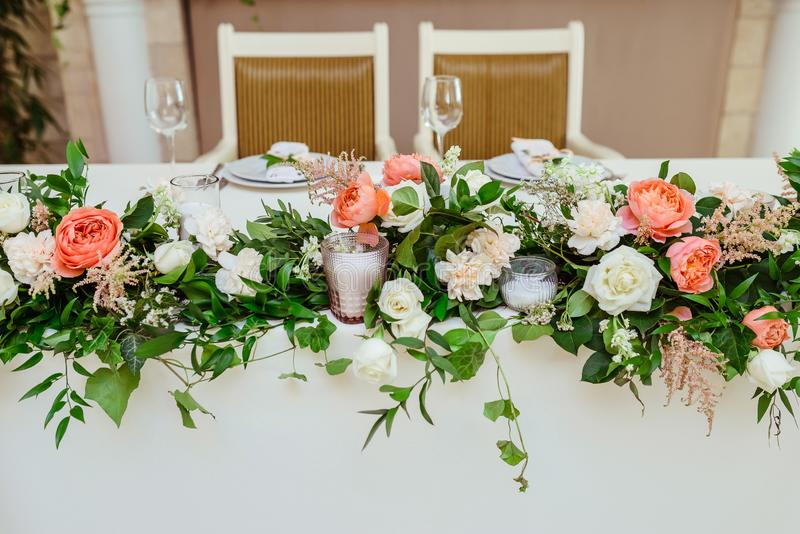 Hochzeitspräsidium Große, lange Zusammensetzung von den frischen Blumen- und Glaskerzenständern stockbilder