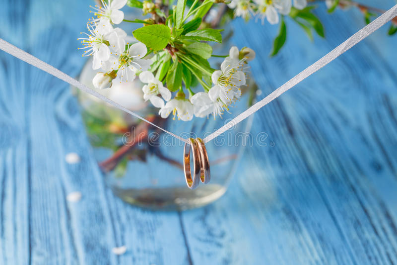 Hochzeitsringe auf einem Zweig Frühlingsblumenstrauß von Kirschblumen stockfotos