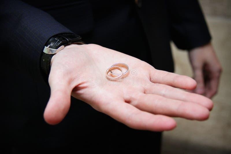 Hochzeitsringe in der Hand stockfotografie