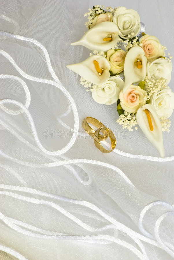 Hochzeitsringe und -blumen über Schleier stockfotografie