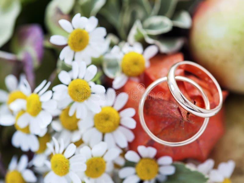 Hochzeitsringe und -blumen stockfoto