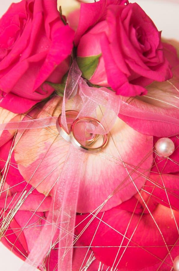 Hochzeitsringe und -blumen im weichen Fokus stockfotografie