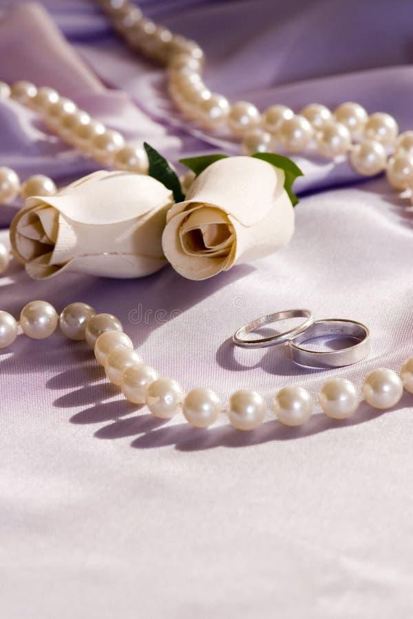 Hochzeitsringe und -rosen stockfoto