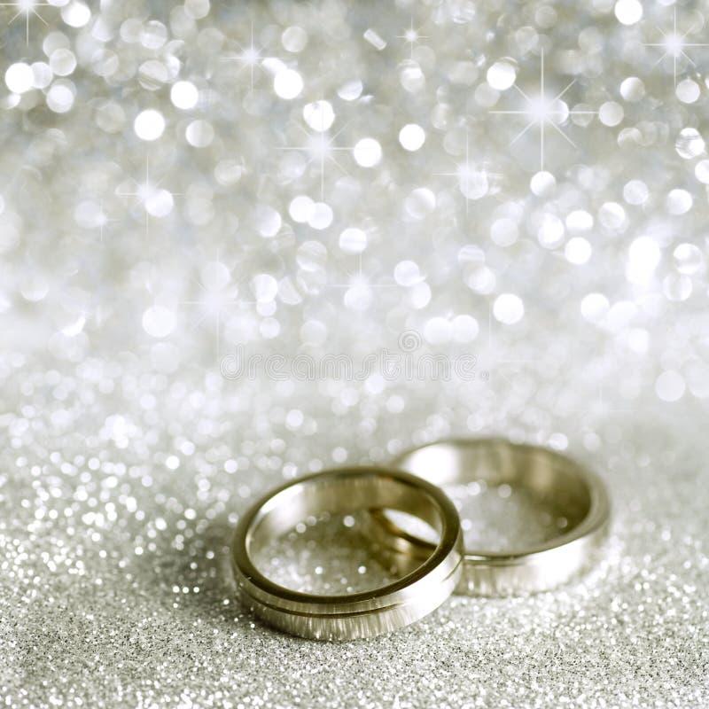 Hochzeitsringe und -sterne im Silber stockbild
