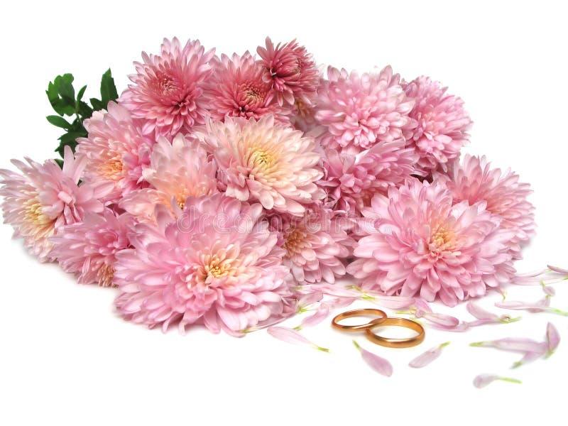 Hochzeitsringe vor Blumen lizenzfreie stockfotografie