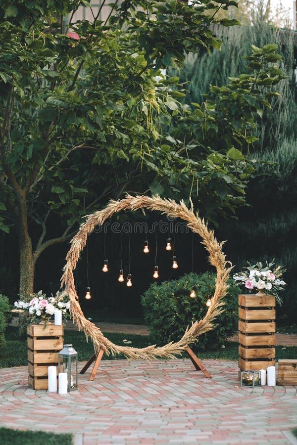 Hochzeitsrundbogen in der rustikalen Art verziert mit Grasheu-Feldfarbe und Retro- Glühlampen Nahe den Holzkisten stockfoto