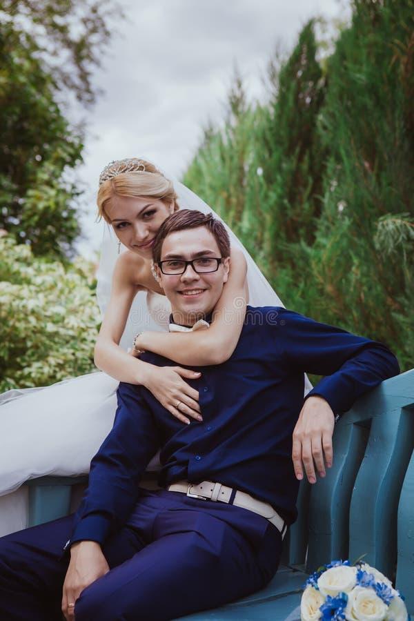 Hochzeitsschuß der Braut und des Bräutigams sitzen auf Bank im Park lizenzfreie stockfotografie