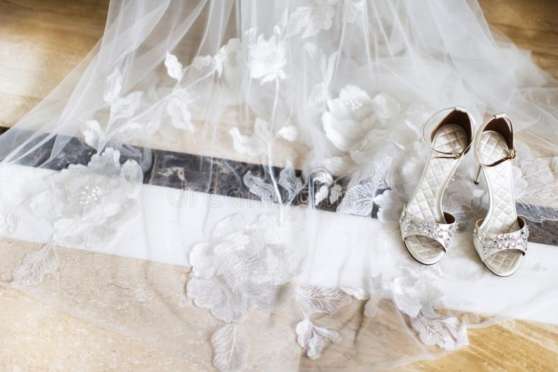 Hochzeitsschuhe mit Juwelen auf dem Brautschleier stockbilder