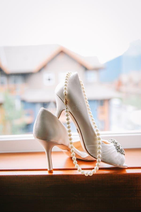 Hochzeitsschuhe und Perlenhalskette stockfotos