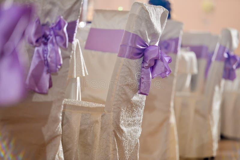 Hochzeitsstühle mit purpurrotem Bogen lizenzfreie stockfotos