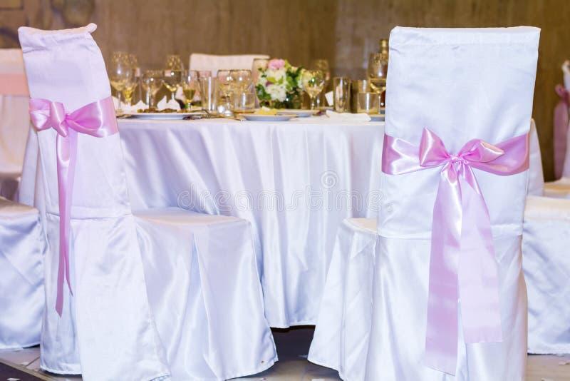Hochzeitsstühle mit rosa Bändern lizenzfreie stockbilder