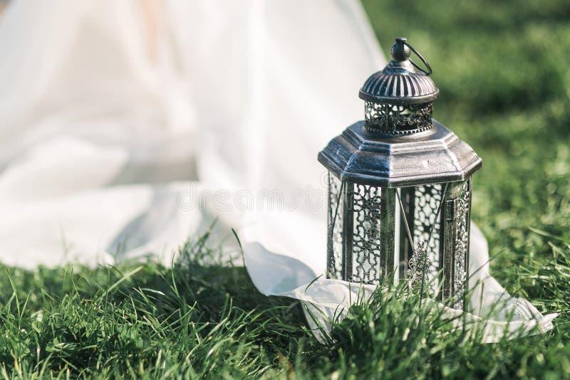 Hochzeitsstilllebenschwarzlaterne auf Gras und weißes tule in der rustikalen Art stockfoto