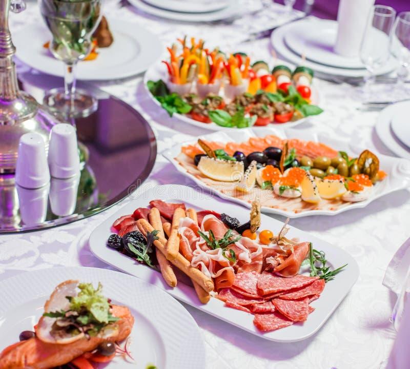 Hochzeitstafel gedient mit geschmackvollen Mahlzeiten, kaltes Fleisch der Antipastoservierplatte, Fischservierplatte, Käseservier lizenzfreie stockfotos