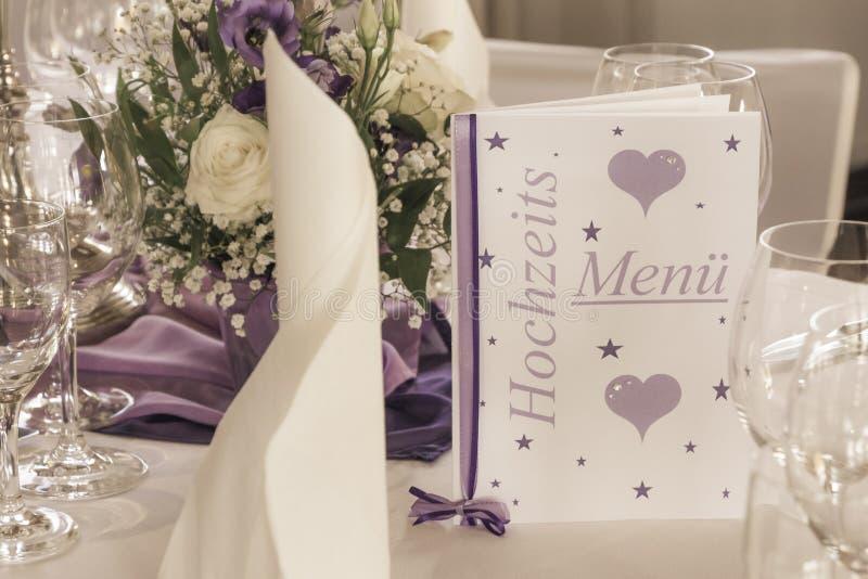 Hochzeitstafel mit Menükartenservietten und -blumen lizenzfreies stockfoto