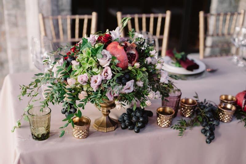 Hochzeitstafeldekoration mit den rosa Blumen, dem Granatapfel und dem Grün stockbilder