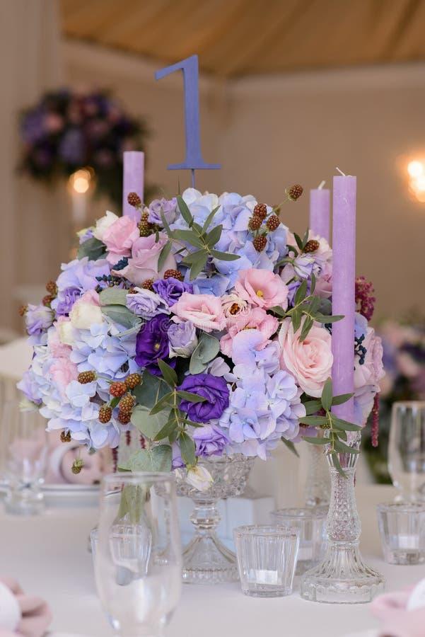 Hochzeitstafeldekoration mit den violetten, blauen, rosa Blumen und dem Grün lizenzfreie stockfotos