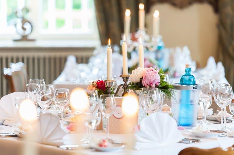 Hochzeitstafeldekoration mit Kerzen und Blumen stockbild