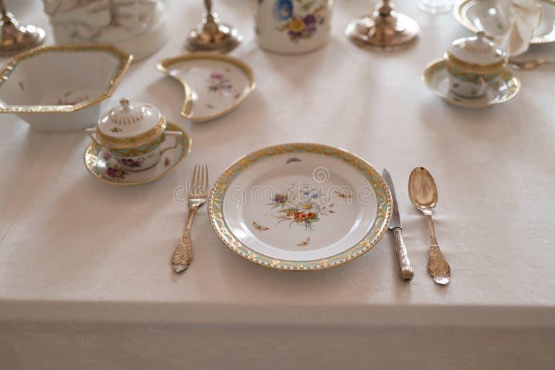 Hochzeitstafeldekoration mit teuren Retro- königlichen Majestätsporzellanservice-Platten und -tischbesteck in einem Palast stockbild