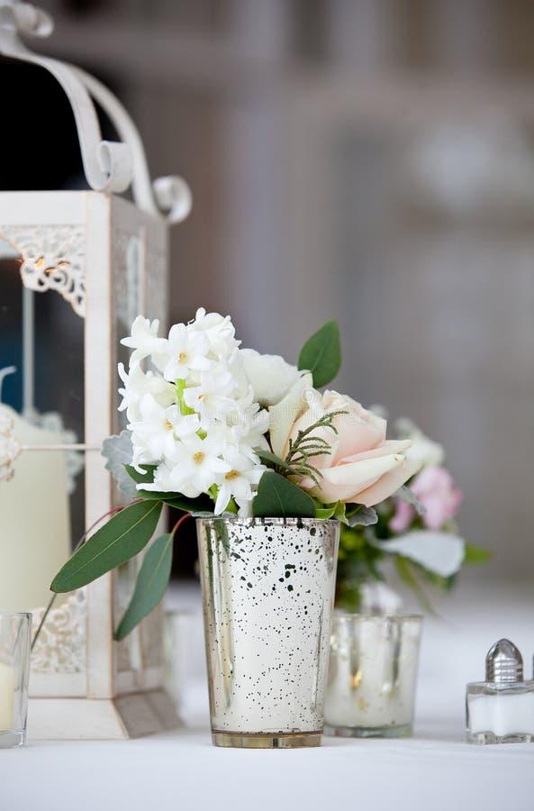 Hochzeitstafeldekorations-Reihe - ein schöner weißer Blumenstrauß von Blumen in einem Klarglas stockfotos