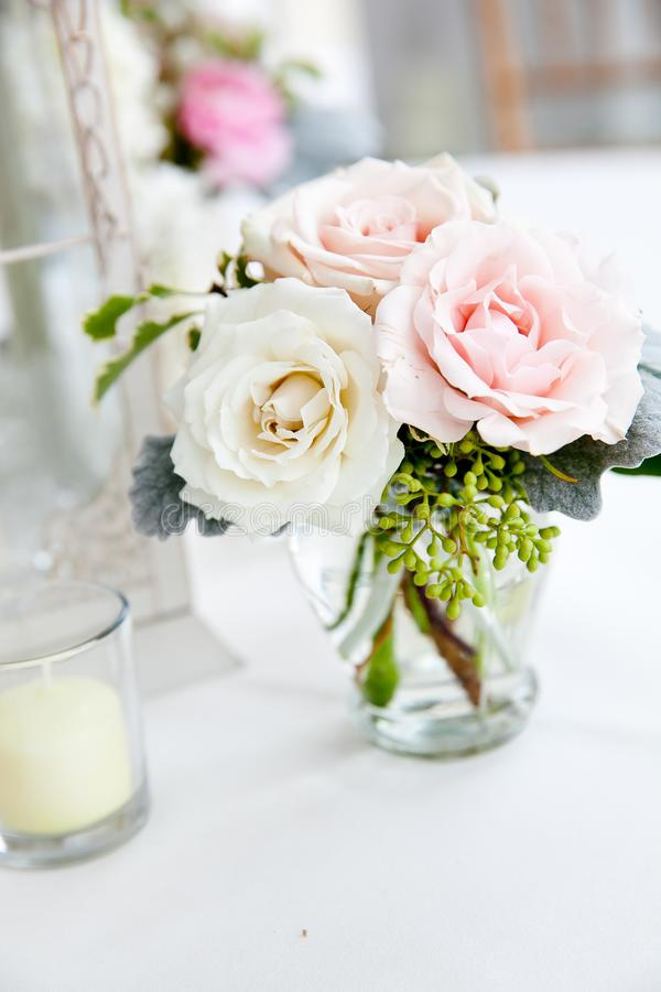 Hochzeitstafeldekorations-Reihe - Rosa- und weißerblumenstrauß von Blumen in den Klarglasvasen lizenzfreie stockfotografie