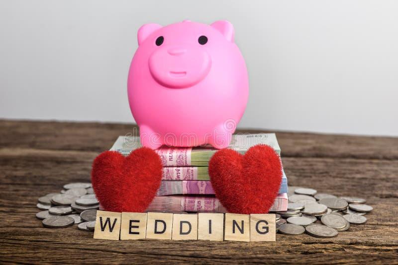 Hochzeitstextwort gemacht mit hölzernen Blöcken und Sparschwein, Herz SH stockfotografie