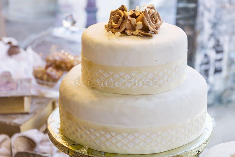 Hochzeitstorte mit goldenen Rosen stockfotografie