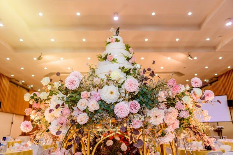 Hochzeitstorte mit verziert mit Blumen und Kerzenständer an der Trauung lizenzfreie stockfotos