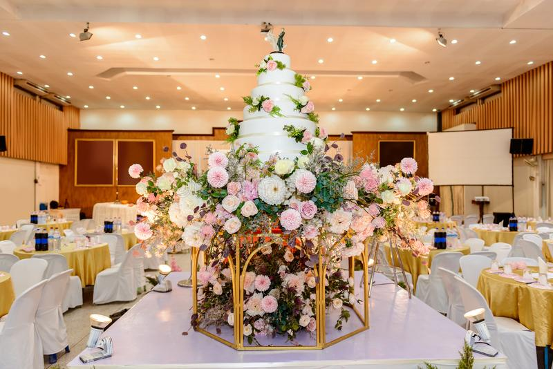 Hochzeitstorte mit verziert mit Blumen und Kerzenständer an der Trauung lizenzfreies stockfoto