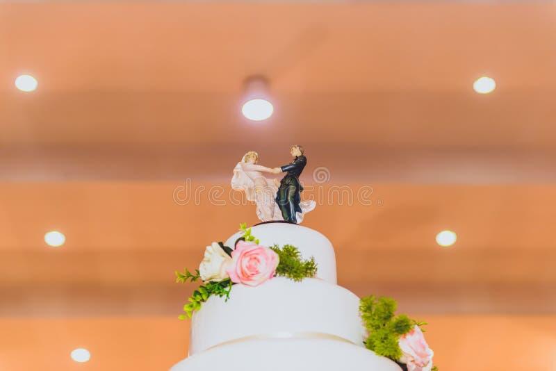 Hochzeitstorte mit verziert mit Blumen und Kerzenständer an der Trauung lizenzfreie stockfotografie