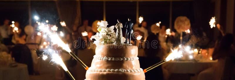 Hochzeitstorte mit Wunderkerzen und undeutlichem Hintergrund stockfoto