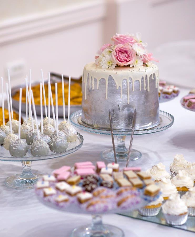 Hochzeitstorte und verschiedenes süßes Lebensmittel auf einer Tabelle lizenzfreies stockbild