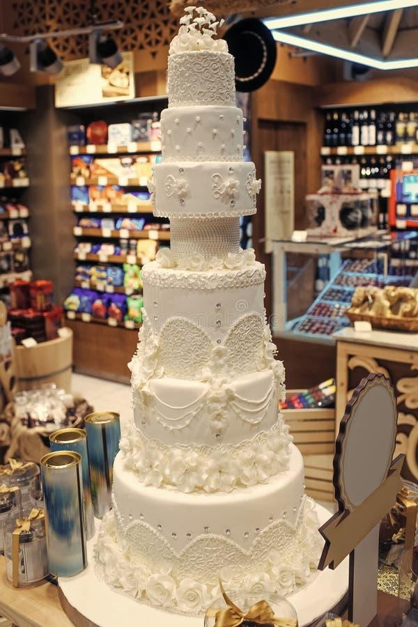 Hochzeitstorte verziert mit Blumen in der Bäckerei lizenzfreies stockfoto