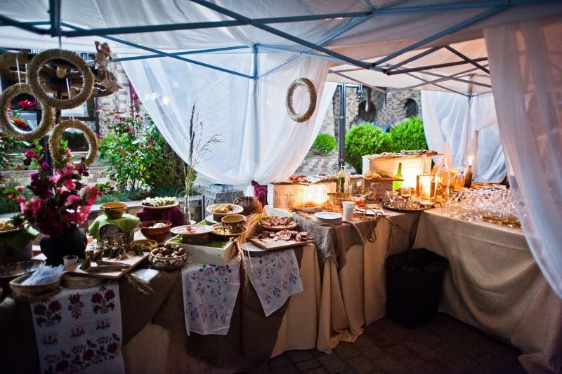 Hochzeitsverpflegungstabelle mit unterschiedlichem Lebensmittel nachts im Freien stockfoto