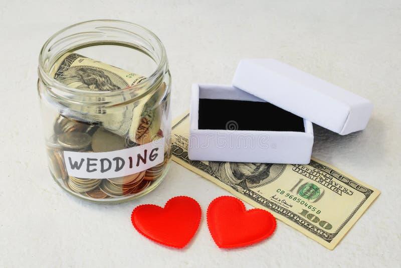 Hochzeitswort, Münzen und Dollarschein in einem Glasgefäß nahe zwei Seidenherzen und im leeren weißen Eheringkasten auf einem wei lizenzfreie stockfotos