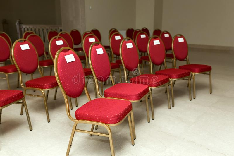 Hochzeitszeremonie in der Banketthalle zuhause Reihen von Stühlen für Gäste an der Hochzeit Ein Stuhl im roten Samt mit Gold und  stockfotografie