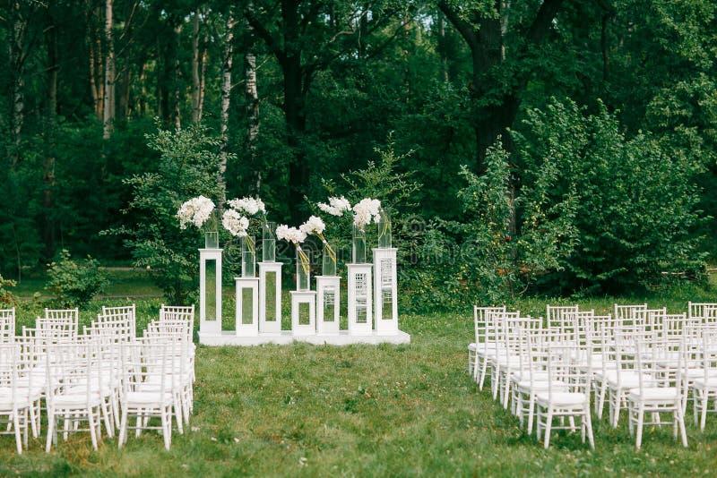 Hochzeitszeremonie in einem schönen Garten weiße Stühle und widergespiegelte Tabellen Glasvase mit Blumen Callalilienamaryllis stockbild