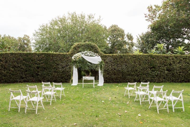 Hochzeitszeremonieeinrichtung Hochzeitsbogen und weiße Stühle auf grünem Rasen im Garten stockfotografie