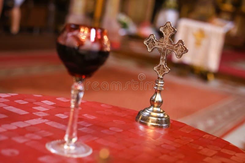 Hochzeitszeremoniekreuz im Hintergrund und in unscharfem Glas der Rebe in der Front Orthodoxe Zusätze der kirchlichen Hochzeit lizenzfreies stockbild
