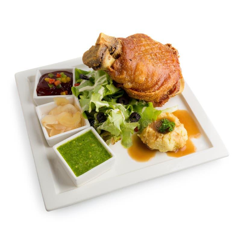 Hock χοιρινού κρέατος στα γερμανικά με τα εύγευστα τρόφιμα σαλτσών που απομονώνονται στο λευκό στοκ εικόνες
