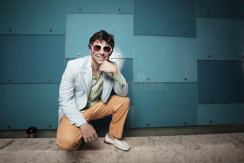 Hockender und lächelnder Mann lizenzfreie stockfotos