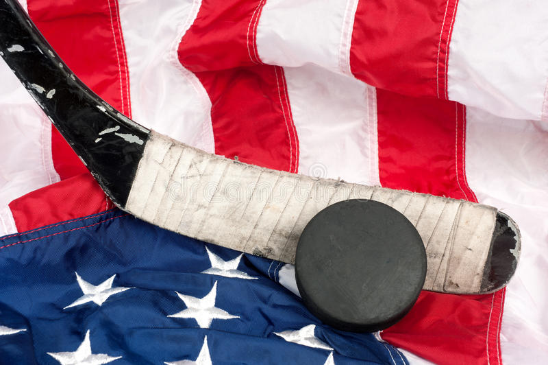 Hockey equipment on an American flag. Hockey equipment including a stick and puck on an American flag to infer a patriotic American sport stock photography