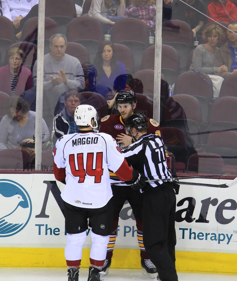 Hockey Fight. Referee stops two hockey players from fighting at the hockey game stock photo