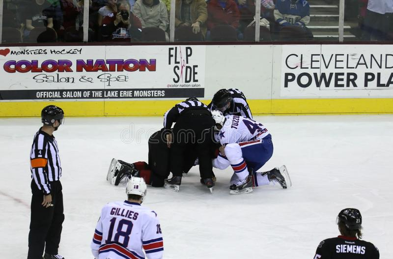 Hockey Fight. Referee stops two hockey players from fighting at the major league professional ice hockey game, Midwest, United States stock image