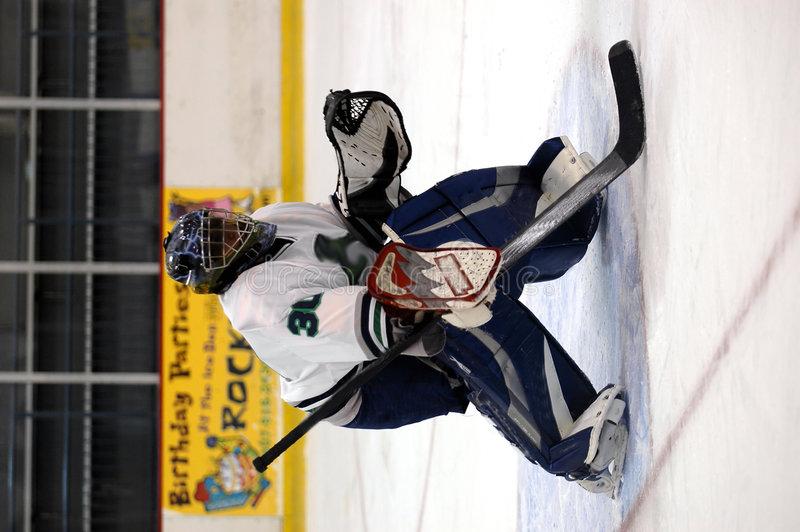 Hockey goalie. A teen/young adult hockey goalie on the ice royalty free stock image